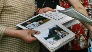 A woman shows photos of her son at a matchmaking fair in Shanghai, China, on May 20, 2006.