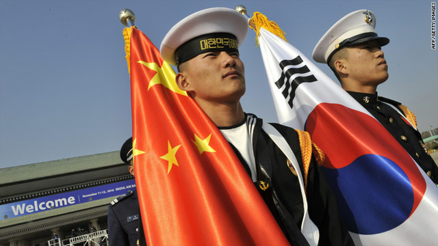 Guards carry the Chinese and South Korean flags at the G-20 but many wonder about the extent of Beijing's ambiitions.