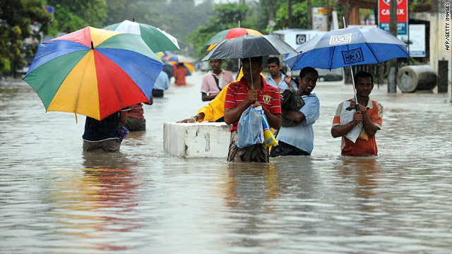 Residents walk along a flooded road in PiliyanDala, a suburb of Colombo.