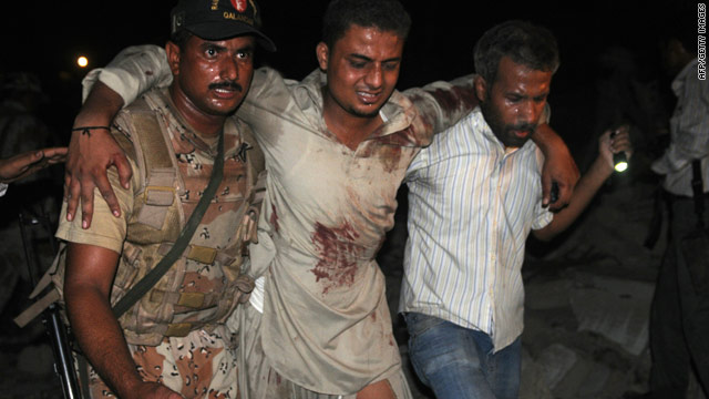 A paramilitary soldier and volunteer help an injured man at a bomb blast site in Karachi on Thursday.
