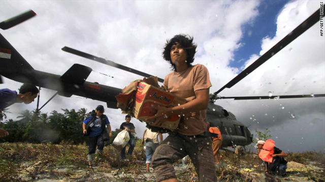 Tsunami victims rush to get relief goods from an Indonesian military helicopter in Malakopak district, South Pagai island, a part of Mentawai islands on November 2, 2010.