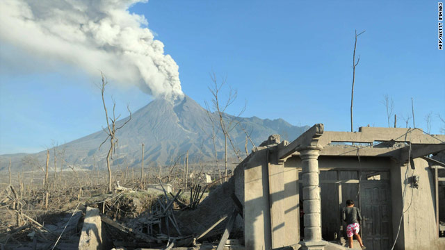 A villager stands amid ash and debris caused by the Mount Merapi volcanic eruption in the Indonesian village of Cangkringan.