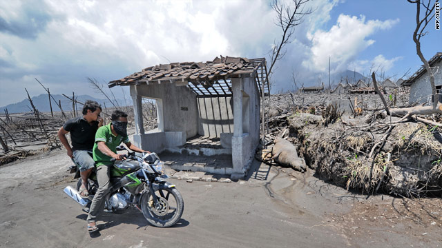 Men ride on a motorcycle November 15 through a village destroyed by the Mount Merapi eruption in Central Java, Indonesia.