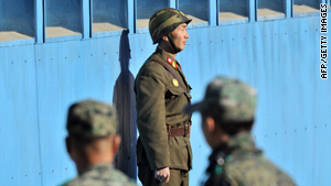 A North Korean soldier, center, stands guard as South Korean soldiers look on in the DMZ on November 3, 2010.