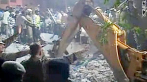 Rescuers try to free people trapped under a collapsed building in Delhi.