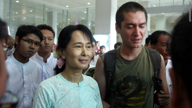 Aung San Suu Kyi holds the hand of her younger son Kim Aris after his arrival at Yangon airport on November 23, 2010.