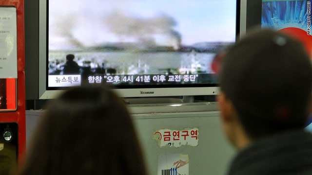 A South Korean couple watch a public television screen broadcasting a report on North Korea's firing over the South Korean border island of Yeonpyeong at a bus terminal in Seoul on November 23