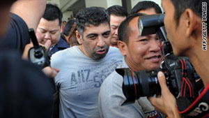 Pakistani national Muhammad Athar Butt (center) is escorted by Thai policemen in Bangkok on December 2.