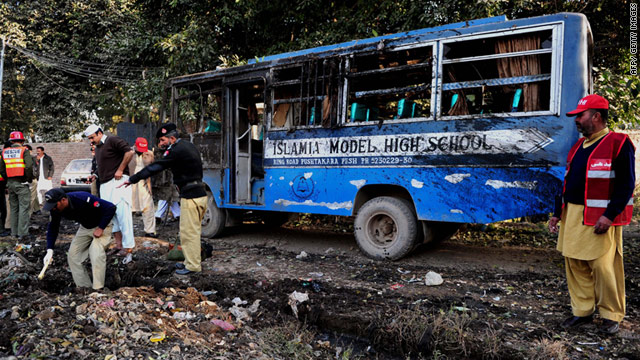 Pakistani security personnel collect evidence at the site of the school bus explosion in Peshawar, Pakistan.