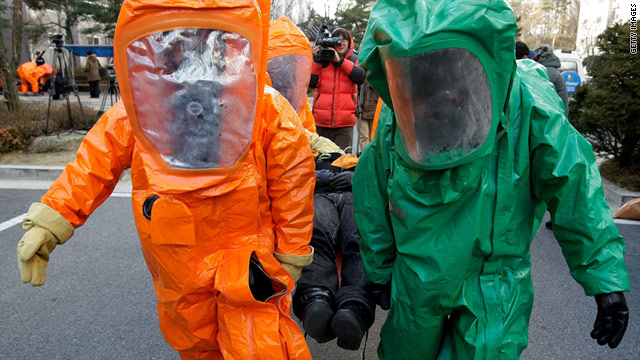 Emergency service personnel in chemical protection suits participate in a civil defense exercise in South Korea, Dec 15, 2010.