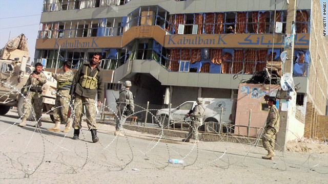 U.S. soldiers and Afghan security forces stand guard at the site of a bombing in front of a branch of Kabul Bank in Kandahar.