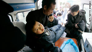 Family members carry an injured child to an ambulance.