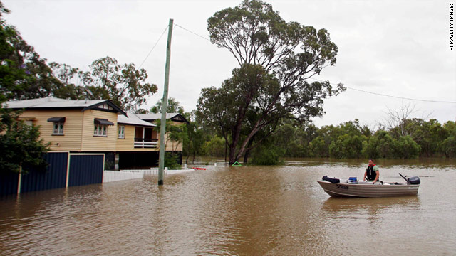 A resident evacuates his flooded home by boat in the country town of Chinchilla in Queensland.