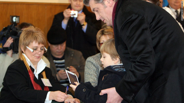 Ukrainian President Victor Yushchenko receives his voting ballot with his son at a polling station in Kiev on January 17, 2010.