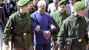 Mehmet Ali Agca pictured in 2006 as he is led, handcuffed, into a courthouse.