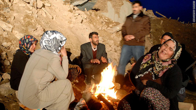 Quake survivors gather around a fire near the ruins of their homes.