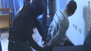 One of the suspects is cuffed by Spanish police.