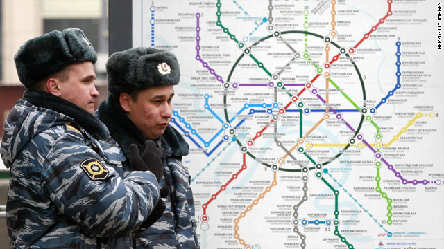 Russian police stand next to a map of Moscow's subway system.