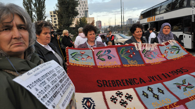 Bosnian Muslim women from Srebrenica hold a hand-woven carpet with the names of their killed relatives embroidered on it.