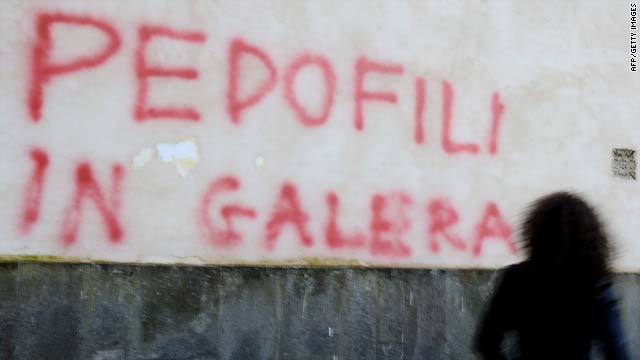 "A woman walks past graffiti reading ""Pedophiles go to jail"" on a wall of the Church of St. Eutizio in Soriano, Italy, on Easter Monday."
