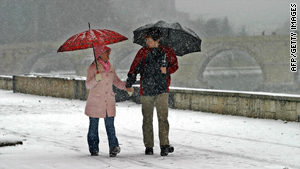 A couple strolling on the embankment of the river Vardar, enjoying the snowfall that turned the city white.