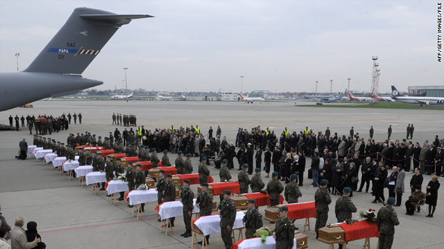 Soldiers and family members stand by the coffins of 25 victims of the April plane crash that killed Poland's president.