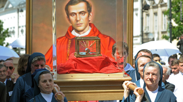 Nuns carry relics of Jerzy Popieluszko in front of his portrait in Warsaw Sunday in a procession after a beatification mass.