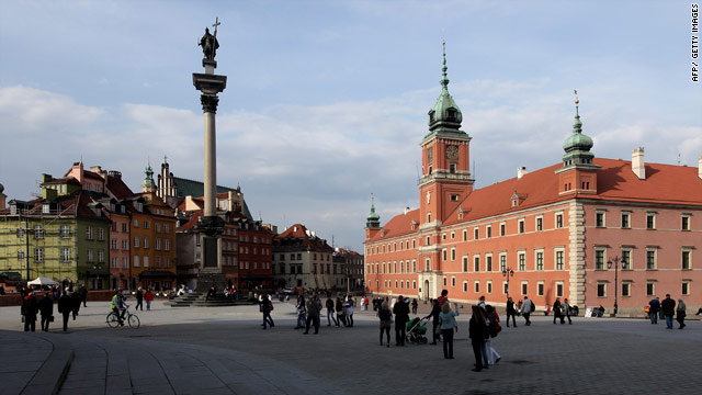 People walk across Zamkowy Square at the entrance to the city's Old Town, Warsaw, Poland.