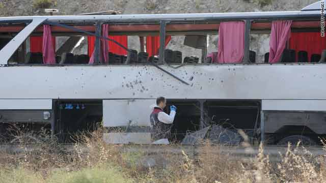 A man inspects the wreckage of a military bus after a roadside bombing, killing four people including a girl in Istanbul  Tuesday.