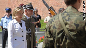 Secretary of State Hillary Clinton pauses to honor murdered military officers Saturday in Krakow, Poland.