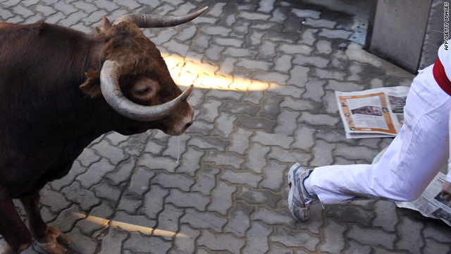 A participant runs ahead of a Jandilla fighting bull name Capuchino on the fourth bull run of the San Fermin festival, on July 10, 2009, in Pamplona, northern Spain.