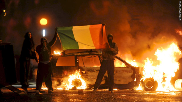Cars burn during rioting in North Belfast on Monday.