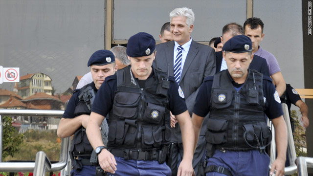 Police escort Central Bank Governor Hashim Rexhepi out of the Kosovo Central Bank compound in Pristina on July 23, 2010.