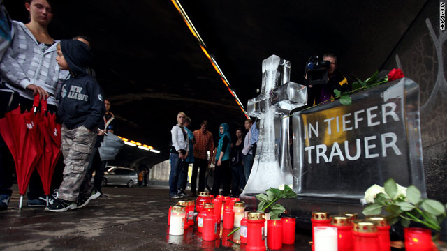 People pay their respects on Monday in front of a make-shift memorial to the festival goers who died in a stampede on Saturday.