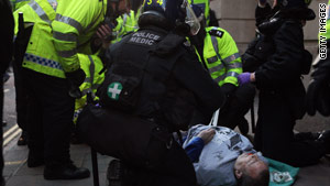 Ian Tomlinson is treated by police officers shortly after collapsing during the G-20 protests.