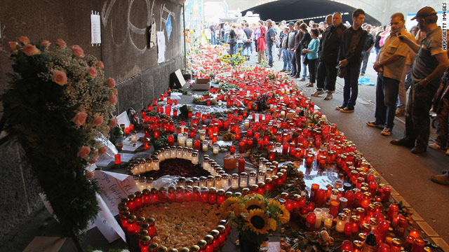 Mourners gather on Tuesday at the German underpass where dozens of people were crushed.