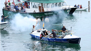 The crew celebrates as it approaches the Isles of Scilly after spending 43 days on the ocean.