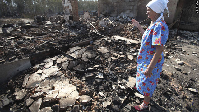 A Russian woman surveys the remains of her burnt out home in Voronezh on August 1, 2010.