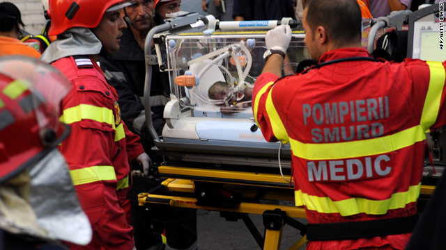 Medics evacuate a newborn baby injured by a fire at the Giulesti maternity ward in Bucharest on Monday.