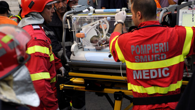 Rescuers tend to a newborn injured by a fire at the Giulesti Maternity Hospital in Bucharest, Romania, on Monday.