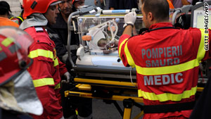 Emergency workers evacuate an infant injured in a hospital fire on August 16, 2010.