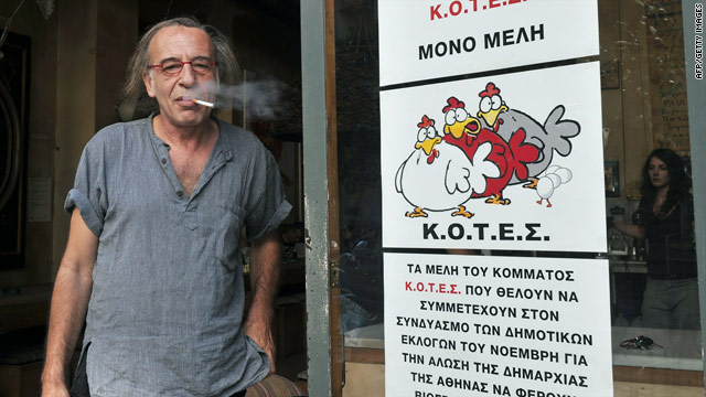 Nikos Louvros, who heads a pro-smoking group, smokes in the entrance to his Athens bar.