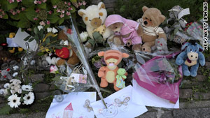 Toys and flowers lie in tribute outside a house where the bodies of three babies were found.