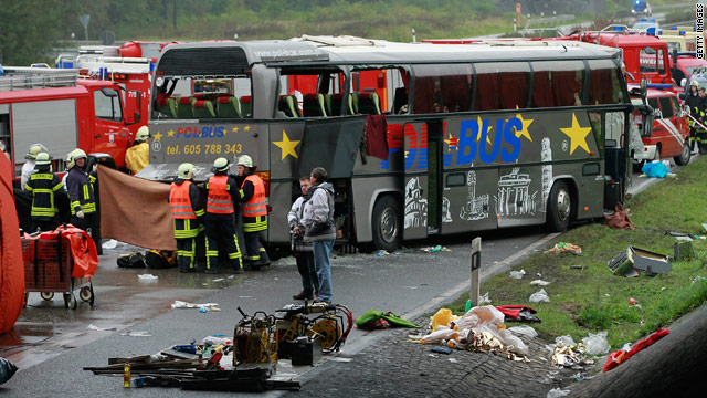 Firefighters and rescue workers stand at the site of a tour bus crash Sunday near Berlin, Germany.