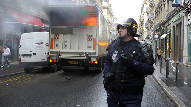 A French police officer runs past a burning truck in Lyon on October 20, 2010.