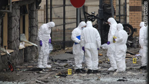 Police forensics officers inspect the scene of a car bombing in South Armagh in April 2010.