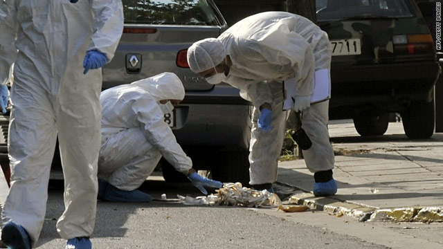 Police investigators search  the scene of the controlled explosion outside of the ACS courier offices in Athens, Nov. 4, 2010.