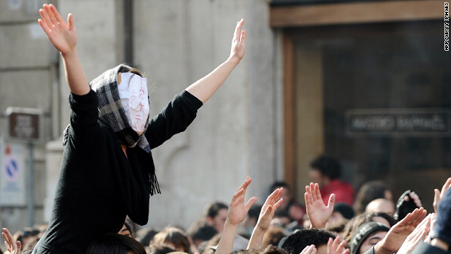 "A student, wearing a mask, reading: ""I was cut,"" protests in front of the Italian Lower House in Rome on Thursday."