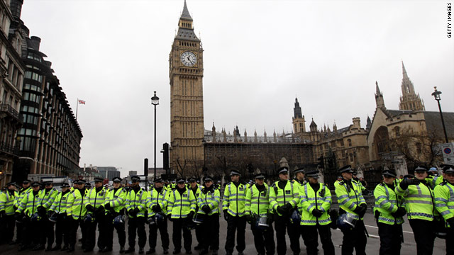 A line of police officers stand guard outside the Houses of Parliament in London as students protest against cuts.