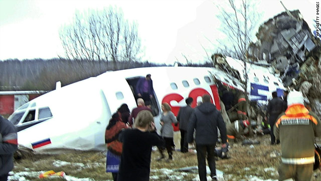 Rescuers move among passengers after a plane crash-landed Saturday at Moscow's Domodedovo airport.